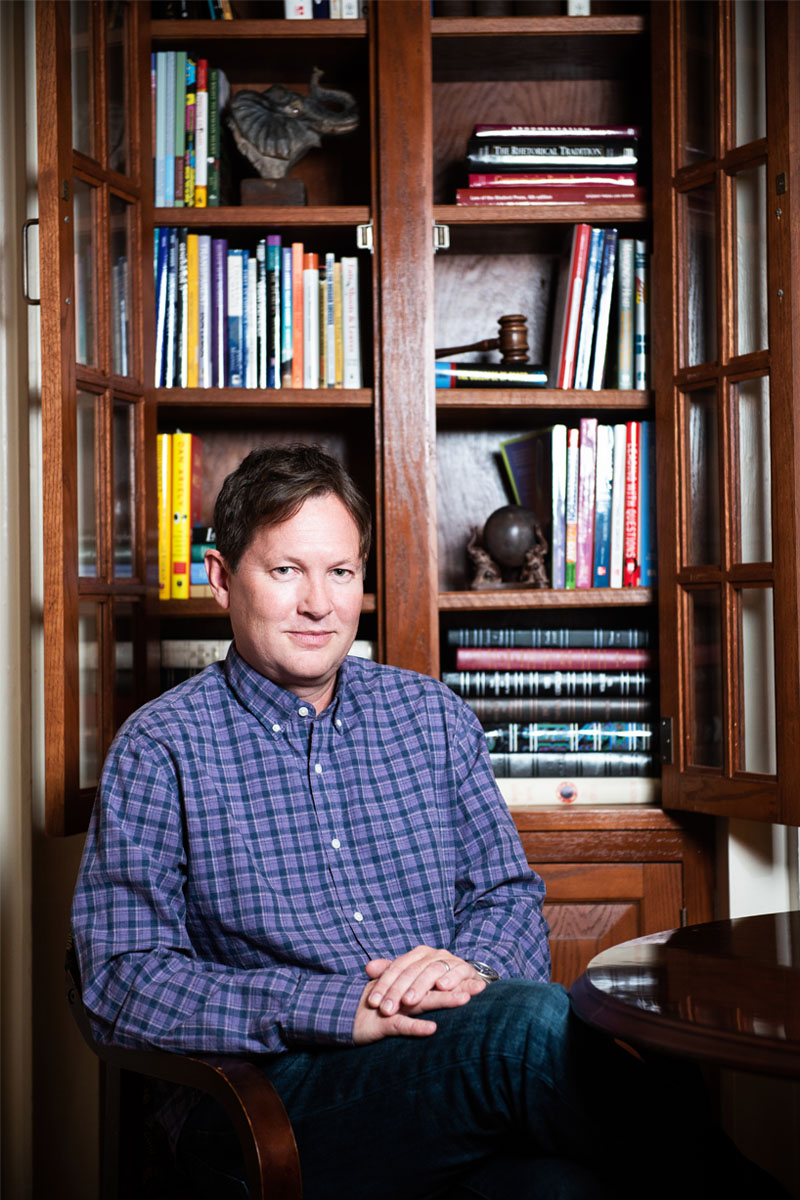 Lars Anderson sits in front of an open, brown bookcase.